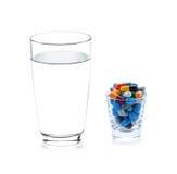 Glas water en pillencapsules Stock Afbeeldingen