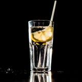 Glas water met citroen en stro op zwarte achtergrond Royalty-vrije Stock Afbeelding