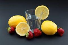 Glas water met citroenen en aardbeien op zwarte achtergrond Stock Afbeeldingen