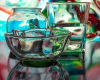 Glas water met daling en gekleurde achtergrond royalty-vrije stock foto's