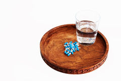 Glas water met geneesmiddelen in capsules op dienblad Stock Fotografie