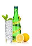 Glas water met ijs, fles, die band, citroen en munt meten Stock Afbeelding