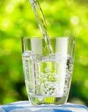 Glas water op aardachtergrond Stock Afbeeldingen