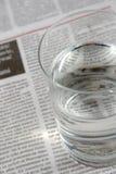 Glas water op een krant Stock Afbeelding