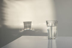Glas of water with reflections. Against the wall and on the table stock photography