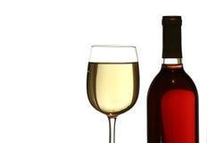 Glas weißer Wein, mit Rotweinflasche Stockbild