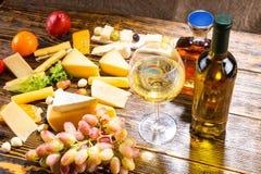 Glas Weißwein auf Tabelle mit verschiedenen Käsen Stockfoto
