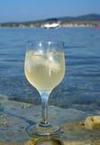 Glas Weißwein durch die Küste Lizenzfreie Stockfotos