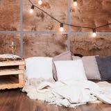 Glas Weißwein im modernen Dachbodeninnenraum mit heller Girlande auf hölzerner Wand Stockfoto