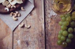 Glas Weißwein, Trauben, Acajounüsse und Weichkäse Stockbild