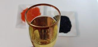 Glas weißer Sekt gegen schwarzen und roten Kaviar stockbild