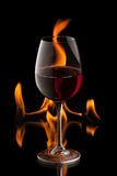 Glas Wein auf schwarzem Hintergrund mit Feuerspritzen Stockfotos
