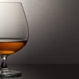 Glas Weinbrand über grauem Hintergrund Lizenzfreie Stockbilder