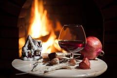 Glas Weinbrand, Kerze, Granatapfel, brennender Kamin Lizenzfreie Stockfotos