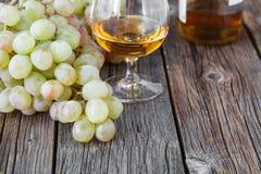 Glas Weinbrand mit Bürste von Trauben auf Tabelle, Erntefeiertag Lizenzfreies Stockfoto