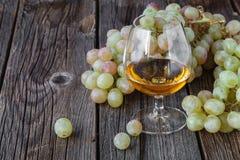 Glas Weinbrand mit Bürste von Trauben auf Tabelle, Erntefeiertag Stockfotografie