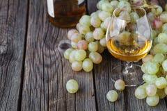 Glas Weinbrand mit Bürste von Trauben auf Tabelle, Erntefeiertag Stockbild