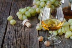 Glas Weinbrand mit Bürste von Trauben auf Tabelle, Erntefeiertag Lizenzfreie Stockbilder