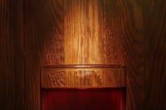 Glas Whisky auf dem alten hölzernen Hintergrund mit Strahl des Lichtes Lizenzfreies Stockfoto