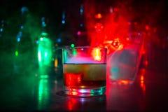 Glas Whisky auf hölzerner Stangennahaufnahme mit Flaschen verwischte Ansicht über dunklen Hintergrund mit Licht und Rauche Einzel Lizenzfreie Stockfotografie