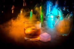 Glas Whisky auf hölzerner Stangennahaufnahme mit Flaschen verwischte Ansicht über dunklen Hintergrund mit Licht und Rauche Einzel Lizenzfreie Stockbilder