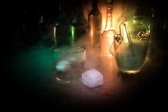 Glas Whisky auf hölzerner Stangennahaufnahme mit Flaschen verwischte Ansicht über dunklen Hintergrund mit Licht und Rauche Einzel Stockbild