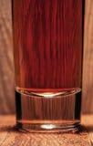 Glas Whisky auf Hintergrund der hölzernen Stange Lizenzfreie Stockbilder