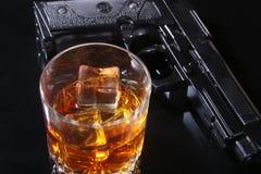 Glas whisky of cognac en kanon op de zwarte spiegellijst Het concept misdadiger stock afbeeldingen