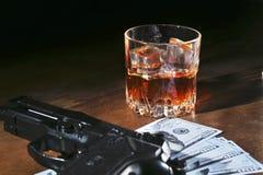 Glas whisky of cognac, kanon, speelkaarten met geld op de zwarte spiegellijst Het concept misdadiger royalty-vrije stock fotografie