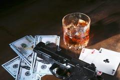 Glas whisky of cognac, kanon, speelkaarten met geld op de zwarte spiegellijst Het concept misdadiger stock foto's