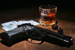 Glas whisky of cognac, kanon, speelkaarten met geld op de zwarte spiegellijst Het concept misdadiger stock afbeelding