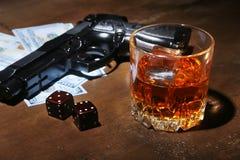 Glas whisky of cognac, kanon, speelkaarten met geld op de zwarte spiegellijst Het concept misdadiger stock fotografie