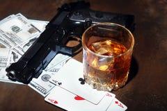 Glas whisky of cognac, kanon, speelkaarten met geld op de zwarte spiegellijst Het concept misdadiger royalty-vrije stock afbeelding