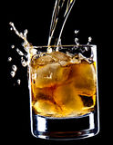 Glas whisky en ijs onder de gietende whisky Royalty-vrije Stock Afbeeldingen