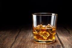 Glas whisky met ijs op houten lijst royalty-vrije stock afbeelding