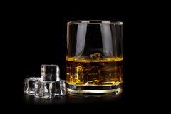 Glas whisky met ijsblokjes op zwarte worden geïsoleerd die Stock Foto