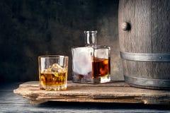 Glas whisky met ijskaraf en vat stock foto