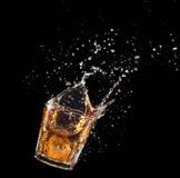 Glas Whisky mit dem Spritzen lokalisiert auf schwarzem Hintergrund Stockfoto