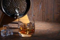 Glas Whisky mit Eis neben einem Fass auf hölzernem backgroun Stockfotografie
