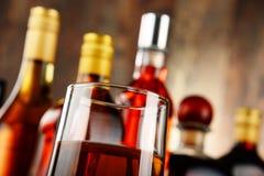 Glas Whisky und Flaschen sortierte alkoholische Getränke stockfotografie