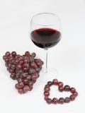 Glas wijn met druiven en hart Royalty-vrije Stock Foto's