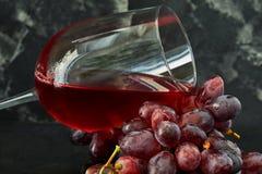 Glas wijn met druiven op een zwarte houten tribune stock afbeeldingen