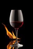 Glas wijn op zwarte achtergrond met brandplons Stock Foto