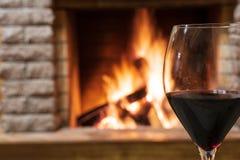 Glas wijn tegen comfortabele open haardachtergrond, hygge concept royalty-vrije stock afbeelding