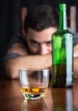 Glas wisky met uit gedronken nadruk en de gedeprimeerde mens stock foto
