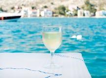 Glas witte wijn op lijst in strandrestaurant met overzeese mening, blauw water en jacht bij achtergrond Stock Afbeeldingen