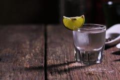 Glas Wodka geschossen mit frischem Kalk Stockbilder
