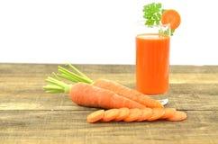 Glas wortelsap, verse wortelen en plakken op houten Stock Fotografie