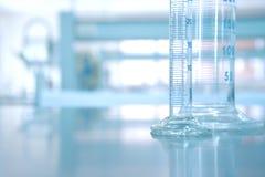 Glas- Zylinder im Forschungschemie-Wissenschaftslabor-backgrou lizenzfreie stockfotografie