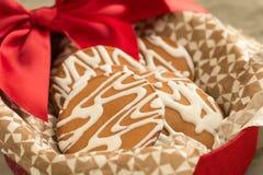Glasade kakor i en röd ask med en pilbåge arkivfoto